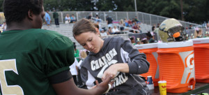ATHLETIC TRAINER JACKIE HARPHAM tapes junior TYSHUN TINNENS' hand before a game.